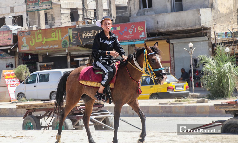 طفل يركب على الحصان في أول أيام عيد الأضحى - 31 تموز 2020 (عنب بلدي / عبد العزيز الصالح )