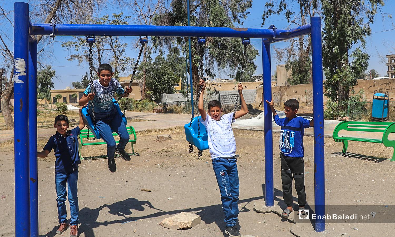 أطفال يلعبون على الأراجيح بمدينة الرقة في أول أيام عيد الأضحى  - 31 تموز 2020 (عنب بلدي / عبد العزيز الصالح )