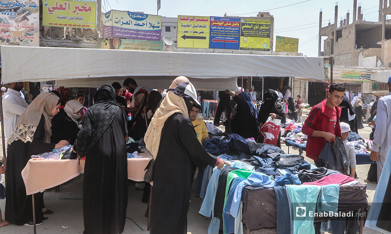 نساء يشترين ألبسة من بسطات في أسواق مدينة الرقة - 30 تموز 2020 (عنب بلدي / عبد العزيز الصالح )