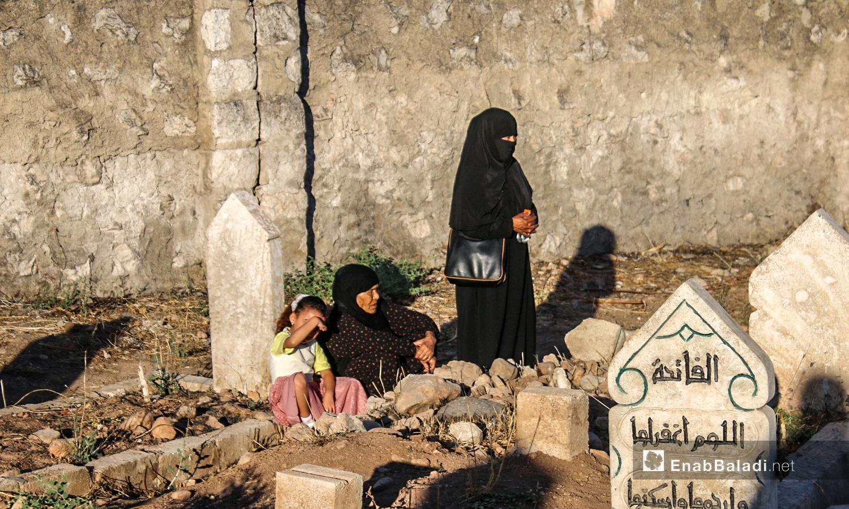 أم تزوح أحد قبور ذويها في بلدة دابق بريف حلب الشمالي  - 31 تموز 2020 (عنب بلدي / عبد السلام مجعان )