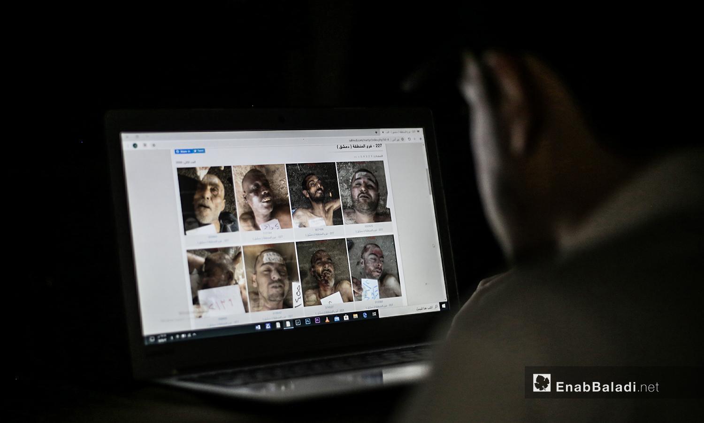 شخص يحاول التعرف على أحد أقربائه المختفي في سجون النظام السوري من خلال الصور المسربة من قيصر - 13 من تموز 2020 (عنب بلدي / يوسف غريبي )