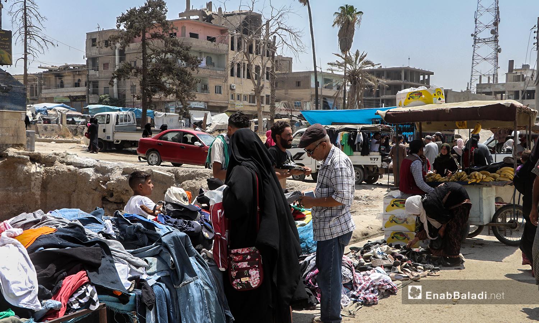 امرأة تشتري الثياب من أحد البسطات في أسواق مدينة الرقة - 30 تموز 2020 (عنب بلدي / عبد العزيز الصالح )