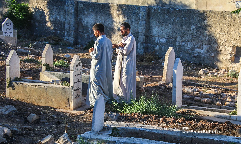 رجلان يزورا أحد قبور ذويهم في أول يوم عيد الأضحى ببلدة دابق في ريف حلب الشمالي  - 31 تموز 2020 (عنب بلدي / عبد السلام مجعان )