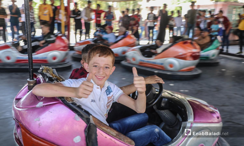 أطفال يلعبون في السيارات الكهربائية بمدينة الرقة في أول أيام عيد الأضحى  - 31 تموز 2020 (عنب بلدي / عبد العزيز الصالح )