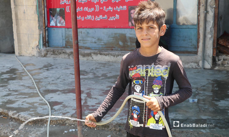 طفل يرش المياه في مدينة الرقة - 11 تموز 2020 (عنب بلدي/عبد العزيز صالح)