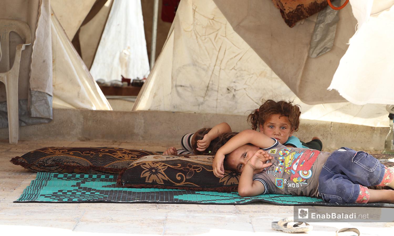 """أطفال مستلقون في خيمتهم في مخيم """"قبتان"""" بريف حلب الشمالي - 17 تموز 2020 (عنب بلدي/عاصم الملحم)"""