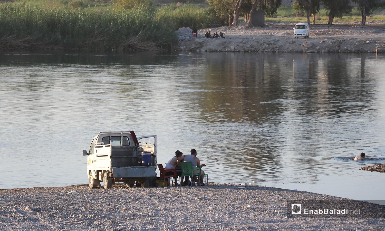 شبان يجلسون على ضفة نهر الفرات في محافظة الرقة - 24 تموز 2020 (عنب بلدي/عبد العزيزالصالح)