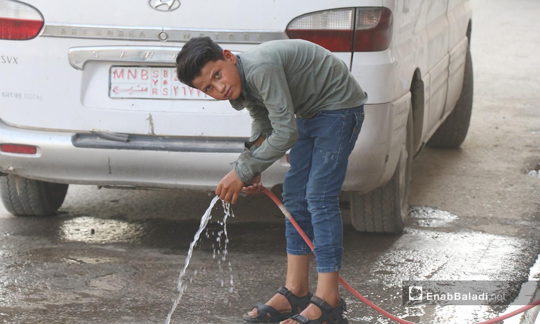 طفل يلهو بالماء في مدينة الرقة - 26 تموز 2020 (عنب بلدي/عبد العزيز الصالح)
