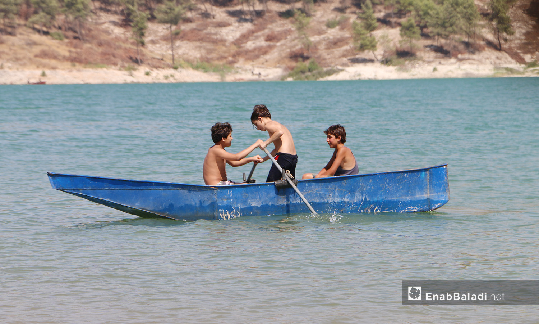 أطفال يقودون قاربًا في بحيرة ميدانكي في عفرين شمالي سوريا - 21 اموز 2020 (عنب بلدي/عبد السلام مجعان)