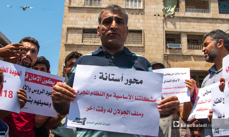 رجل يحمل لافتة لضامني محور أستانة في مظاهرة بمدينة إدلب - 3من تموز 2020 (عنب بلدي/أنس الخولي)