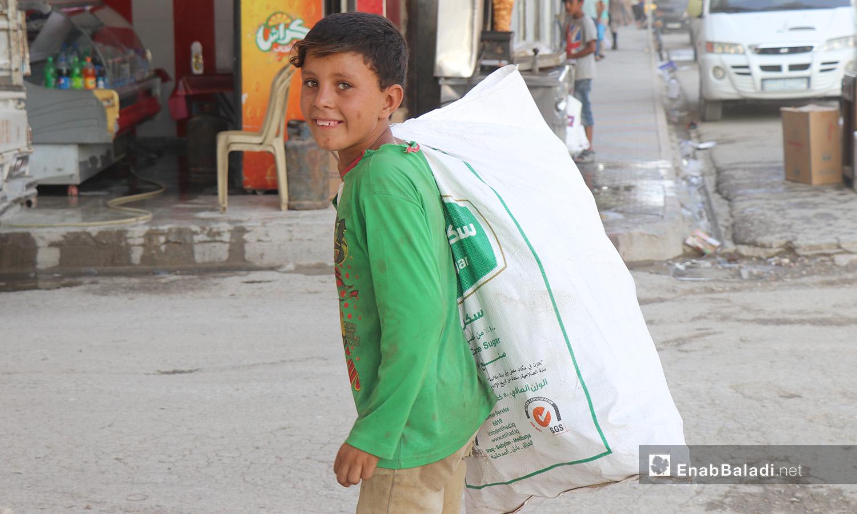 طفل يحمل كيسًا في مدينة الرقة - 26 تموز 2020 (عنب بلدي/عبد العزيز الصالح)