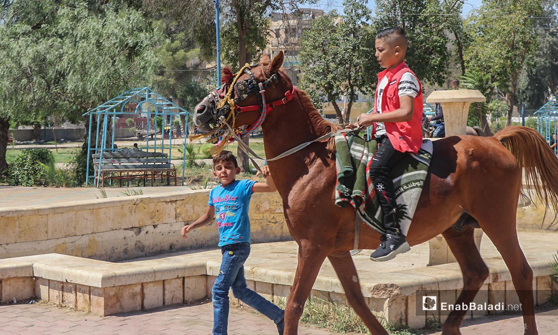 أطفال يركبون على الحصان في أول أيام عيد الأضحى - 31 تموز 2020 (عنب بلدي / عبد العزيز الصالح )