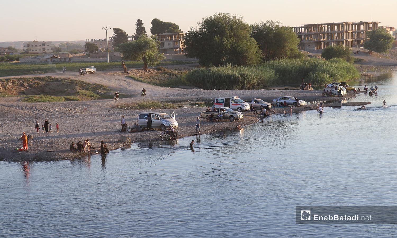أهالي يجلسون على إحدى ضفاف نهر الفرات في محافظة الرقة - 24 تموز 2020 (عنب بلدي/عبد العزيز صالح)