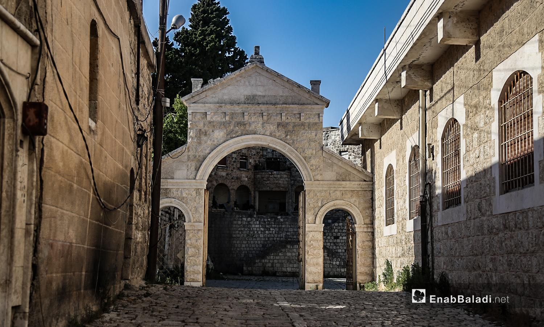 """القوس الحجري الموصل لكنيسة """"مار يوسف"""" في قرية القنية في ريف إدلب الغربي - تموز 2020 (عنب بلدي)"""