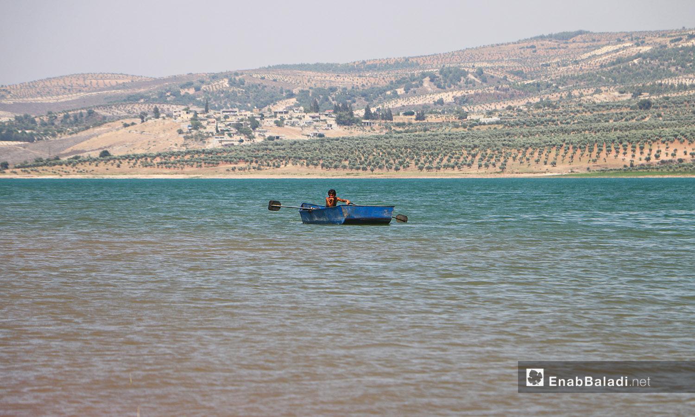 شاب يقود قاربًا في بحيرة ميدانكي في عفرين شمالي سوريا - 21 تموز 2020 (عنب بلدي/عبد السلام مجعان)