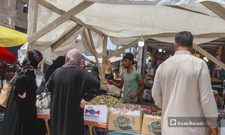 شاب يبيع الحلويات على بسطة في سوق مدينة الرقة قبيل عيد الأضحى - 30 تموز 2020 (عنب بلدي / عبد العزيز الصالح )