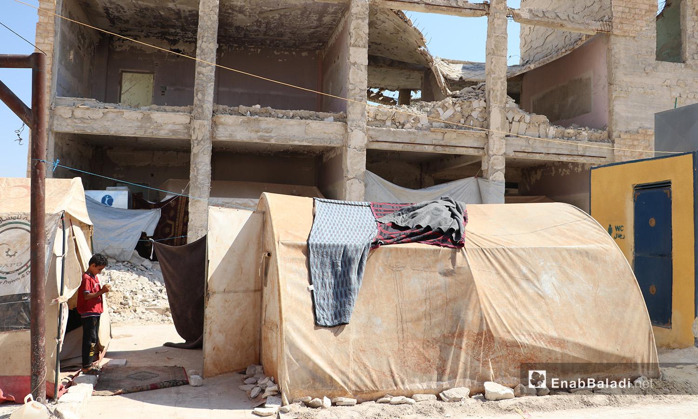 """خيمة نصبت أمام مبنى مهدم في مخيم """"قبتان"""" قرب بلدة أخترين بريف حلب الشمالي - 17 تموز 2020 (عنب بلدي/عاصم الملحم)"""