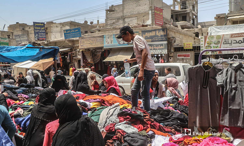 شاب يبيع الألبسة على بسطة في سوق مدينة الرقة قبيل عيد الأضحى - 30 تموز 2020 (عنب بلدي / عبد العزيز الصالح )