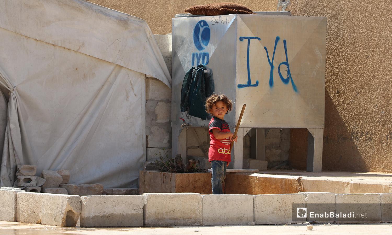 """طفلة صغيرة أمام خزان ماء في مخيم """"قبتان"""" قرب بلدة أخترين بريف حلب الشمالي - 17 تموز 2020 (عنب بلدي/عاصم الملحم)"""