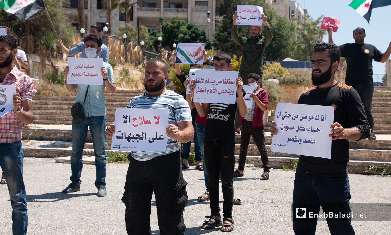 مجموعة شبان يحملون لافتات في وقفة احتجاجية بمدينة إدلب - 17 تموز 2020 (عنب بلدي/أنس الخولي)