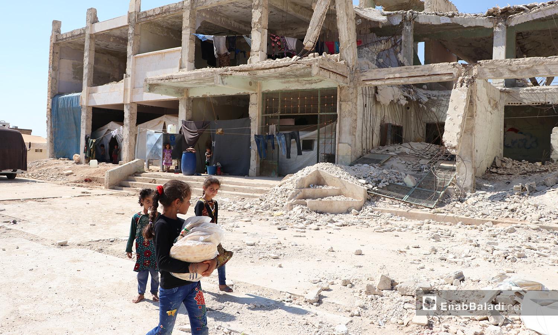 """طفلة تحمل الخبز في مخيم """"قبتان"""" قرب بلدة أخترين بريف حلب الشمالي - 17 تموز 2020 (عنب بلدي/عاصم الملحم)"""