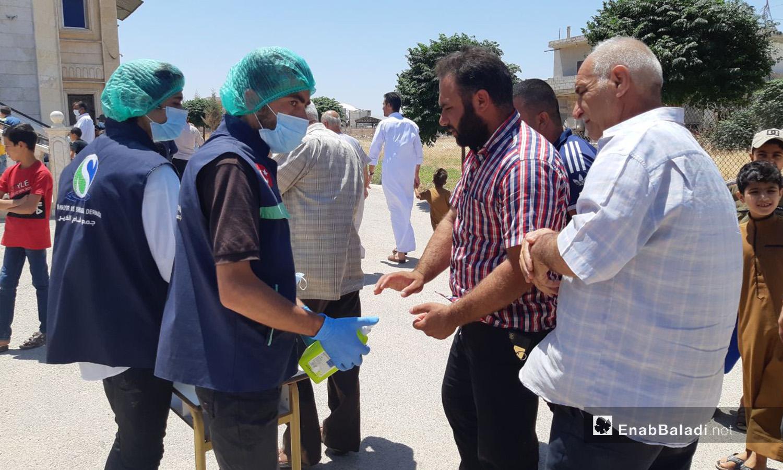 """توزيع كمامات ومعقمات على ابواب بعض المساجد بريف ادلب الشمالي كإجراء وقائي ضد انتشار فيروس """"كورونا المستجد"""" - 7 تموز 2020 (عنب بلدي/إياد عبد الجواد)"""