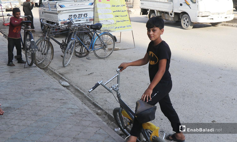 طفل يلهو بالدراجة الهوائية في مدينة الرقة - 26 تموز 2020 (عنب بلدي/عبد العزيز الصالح)