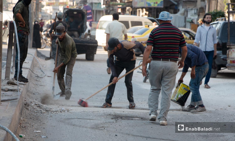عاملون في مجلي مدينة إدلب أثناء ترميم أحد طرقات المدينة - 14 تموز 2020 (عنب بلدي/أنس الخولي)