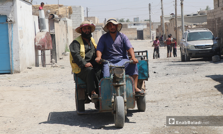 شخصان يركبان شاحنة بثلاث عجلات في مدينة الرقة - 11 تموز 2020 (عنب بلدي/عبد العزيز صالح)