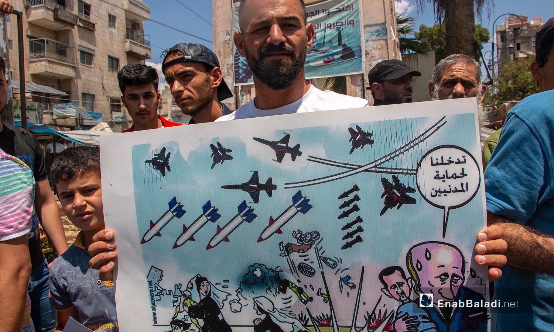 رجل يحمل لافتة عن قصف الطائرات والصواريخ الروسية المدنيين في سوريا - 3 من تموز 2020 (عنب بلدي/أنس الخولي)
