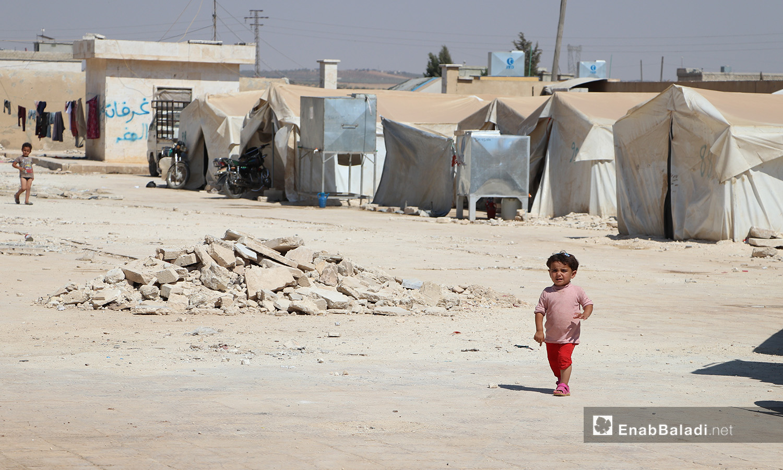 """طفلة صغيرة تسير وحيدة تحت أشعة الشمس في مخيم """"قبتان"""" قرب بلدة أخترين بريف حلب الشمالي - 17 تموز 2020 (عنب بلدي/عاصم الملحم)"""