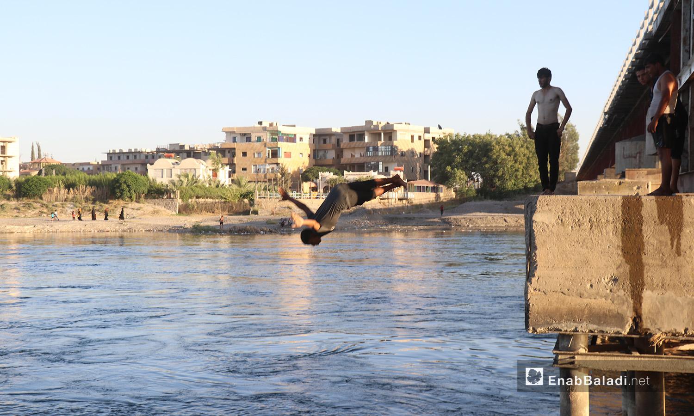 شاب يقفز للسباحة من جسر يمر فوق نهر الفرات في محافظة الرقة - 24 تموز 2020 (عنب بلدي/عبد العزيز صالح)