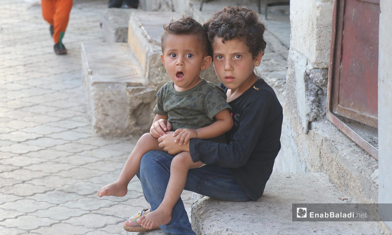 طفل يحمل أخاه الصغير أمام منزلهمن في مدينة الرقة - 26 تموز 2020 (عنب بلدي/عبد العزيز الصالح)