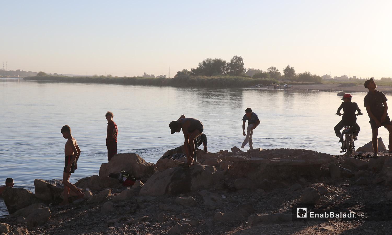 شبان يتجهزون للسباحة في نهر الفرات بمحافظة الرقة - 24 تموز 2020 (عنب بلدي/عبد العزيز الصالح)