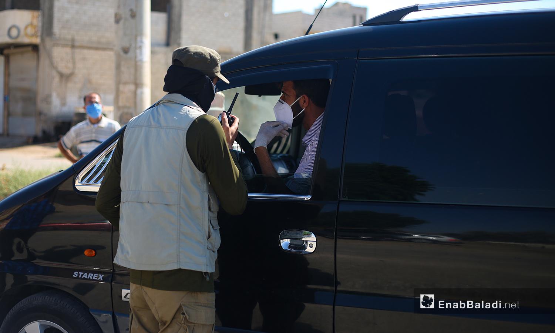 """القوى الأمنية التابعة لـ""""حكومة الإنقاذ"""" تغلق الطرقات الواصلة إلى مدينة سرمين في ريف إدلب ضمن إجراءات الحد من انتشار فيروس """"كورونا"""" - 25 تموز 2020 (عنب بلدي/ يوسف غريبي)"""
