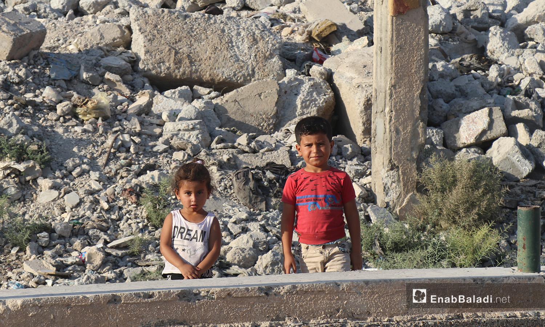 طفلان أمام مبنى مهدم في مدينة الرقة - 26 تموز 2020 (عنب بلدي/عبد العزيز الصالح)