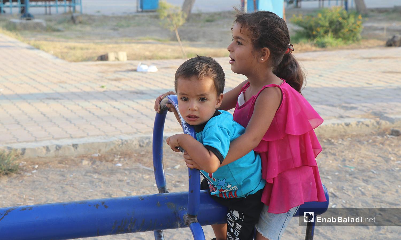 طفلان يلهوان في إحدى حدائق مدينة الرقة - 26 تموز 2020 (عنب بلدي/عبد العزيز الصالح)