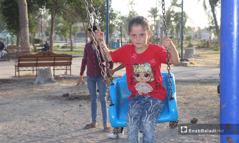 طفلة تركب الأرجوحة في إحدى حدائق مدينة الرقة - 26 تموز 2020 (عنب بلدي/عبد العزيز الصالح)