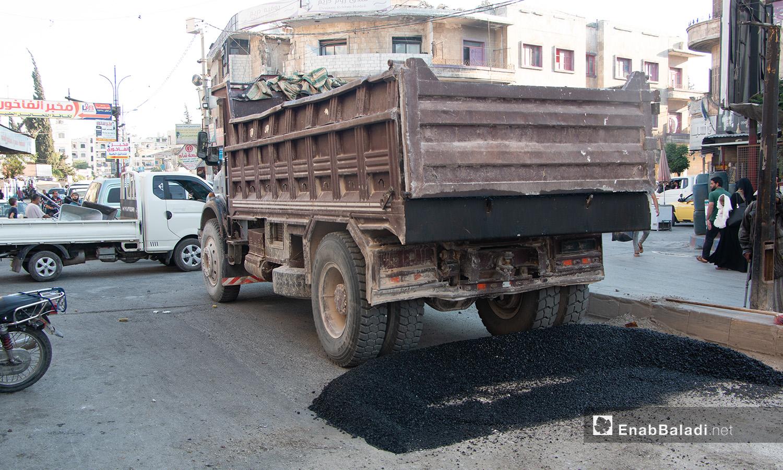 """سيارة تضع كمية من """"الزفت"""" في شوارع مدينة إدلب أثناء أعمال ترميم الطرقات في المدينة - 14 تموز 2020 (عنب بلدي/أنس الخولي)"""