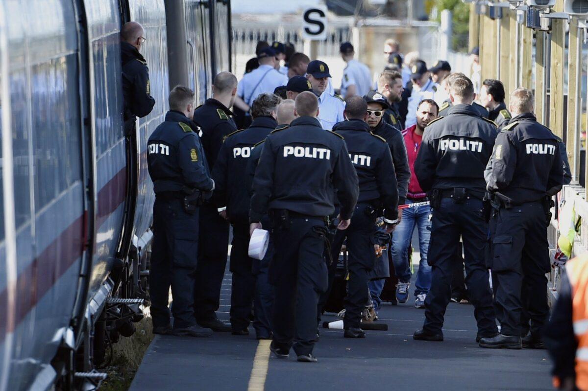 الشرطة الدنماركية تحرس قطارًا مع مهاجرين ، معظمهم من سوريا والعراق ، في محطة قطار رودبي ، جنوب الدنمارك