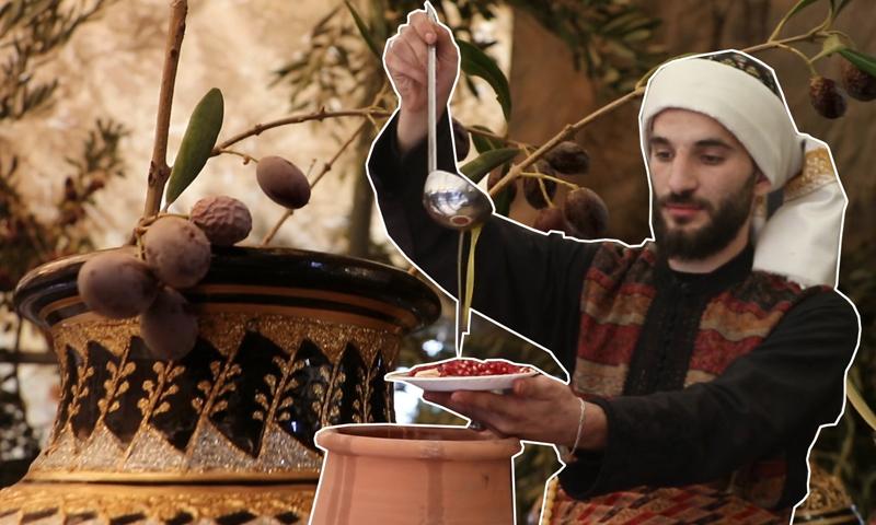 رجل يرتدي ملابس تقليدية سورية ويصب زيت الزيتون- (تعديل عنب بلدي)