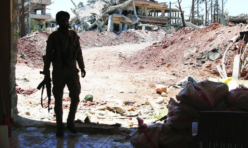 مقاتل يحمل السلاح وخلفه دمار الأبنية في درعا جنوبي سوريا (رويترز)
