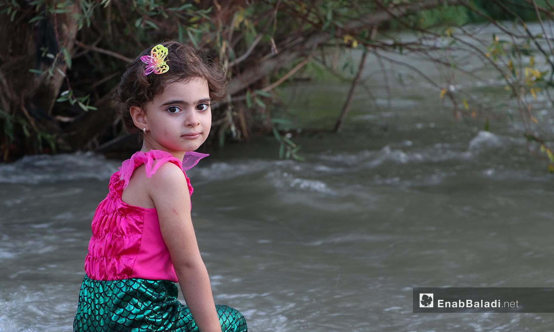 طفلة تجلس على ضفة نهر حنة في عفرين - 7 آب 2020 (عنب بلدي/ عاصم الملحم)