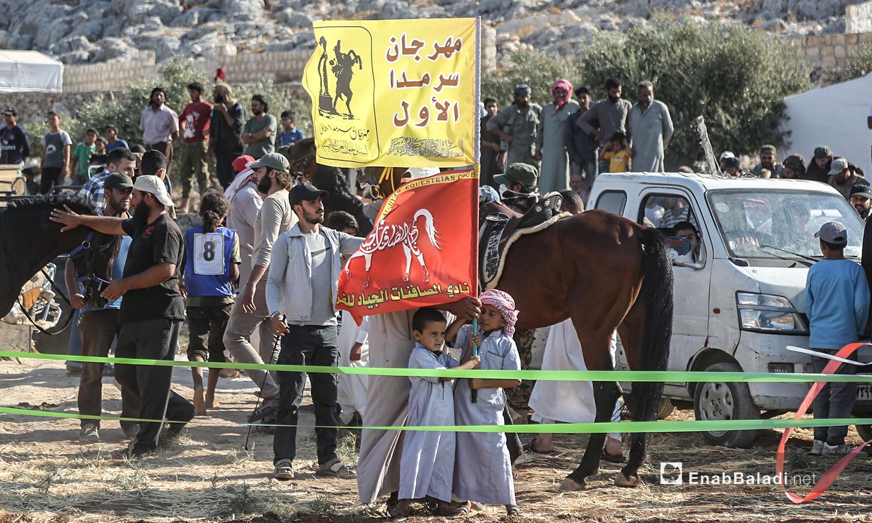 أطفال يحملون راية مهرجان سرمد للخيول العربية الأصيلة في مدينة سرمدا بشمال إدلب - 28 آب 2020 (عنب بلدي / يوسف غريبي)