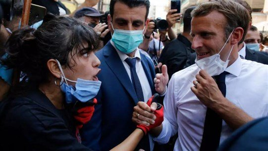 الرئيس الفرنسي إيمانويل ماكرون يستمع لشهادة مواطنة خلال زيارته لشارع مدمر في بيروت - 6 من آب 2020 (AP)