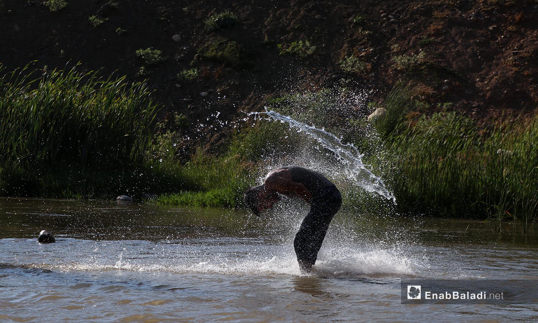 شاب يرمي على نفسه الماء في نهر حنة في عفرين - 7 آب 2020 (عنب بلدي/عاصم الملحم)