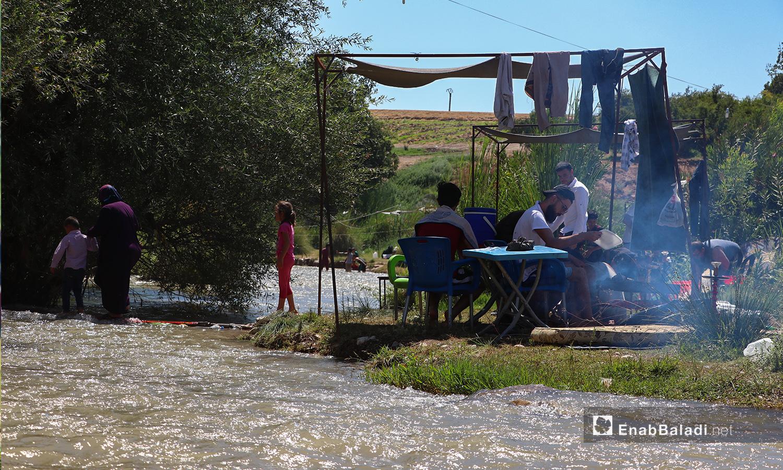 عائلة يحضرون الطعام على ضفة نهر حنة في عفرين - 7 آب 2020 (عنب بلدي/عاصم الملحم)
