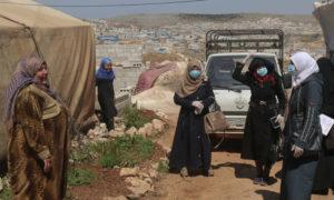نازحون سوريون يرتدون كمامات ويمارسون التباعد الجسدي (OCHA)