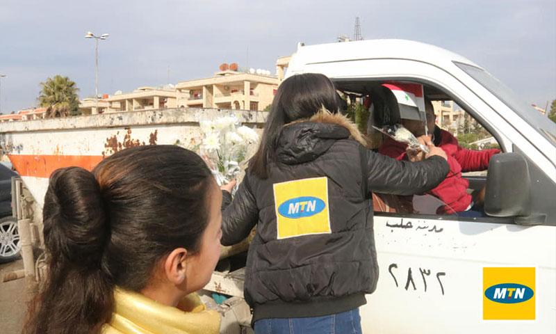شركة MTN توزع الورود احتفالًا بذكرى ستعادة النظام السوري لمدينة حلب (الصفحة الرسمية للشركة في فيس بوك)