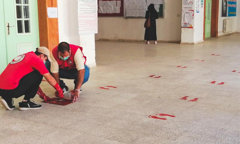 وضع إشارات من قبل عناصر الهلال الأحمر السوري للتباعد المكاني في الدوائر الخدمية - 5 أيلول 2020 (الهلال الأحمر السوري)